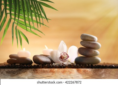 Composition with spa stones and flower on blurred background