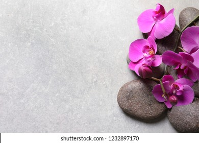 Composition with spa stones and orchid flowers on grey background. Space for text