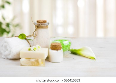Composition of spa wellness products on light wooden background.