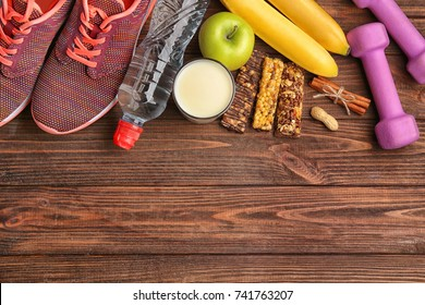 Composition with sport equipment and cereal bars on wooden background
