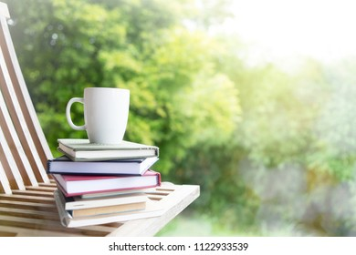 Composition with Stack of books and cup of coffee on blurred green background.