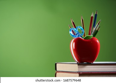 Composition with stationery and apple shaped pencil holder on table near chalkboard,copy space for text.