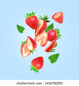 The composition of strawberries on a colored background. Cut strawberries into pieces with copy space. Fresh natural strawberry isolated