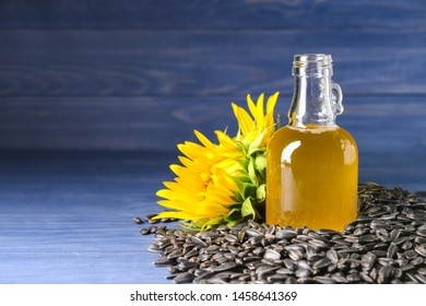 Composition with sunflower oil and seeds on wooden background
