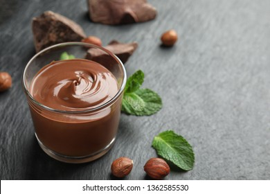 Composition with sweet chocolate mousse in glass on table. Space for text