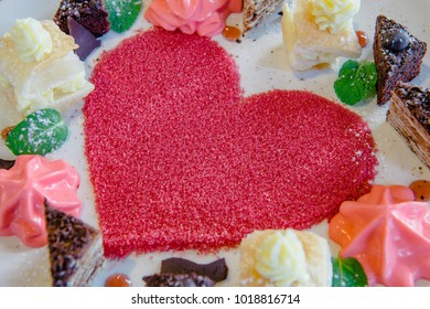 Composition of Sweet Dessert Sugar Heart In between small cakes