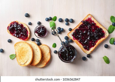 Composition with sweet jam and toasts on wooden background