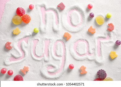Composition with sweets and phrase NO SUGAR written on sugar sand