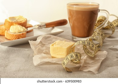 Composition with tasty butter coffee and measuring tape on grey table