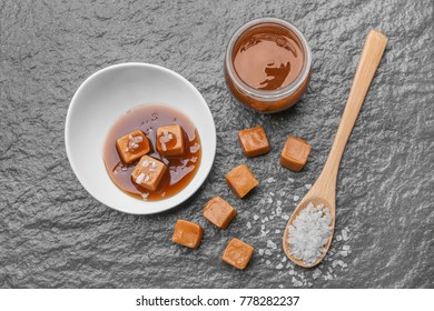 Composition with tasty caramel candies and salt on table