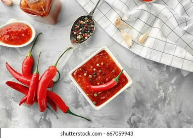 Composition with tasty chili sauce in bowl on table