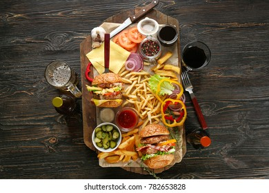 Composition with tasty double burgers and vegetables on wooden table