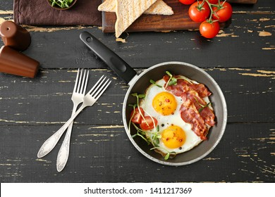 Composition with tasty fried eggs and bacon on wooden table