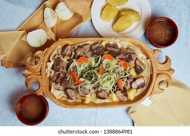 Composition of tasty Kazakh national dish beshbarmak in a wooden plate with kazy, flour tortillas, onions and potatoes