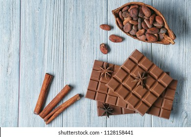 Composition with tasty milk chocolate, cocoa beans and cinnamon sticks on wooden background
