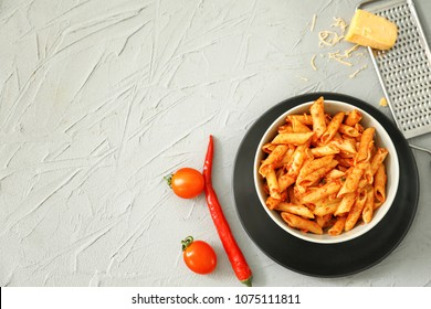 Composition with tasty penne pasta on light textured background