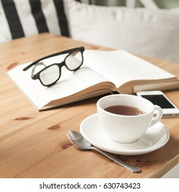Composition with tea cup, book, and mobile phone on wooden table.