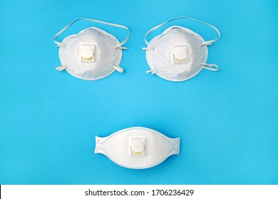 A composition of three medical white sanitary masks in the form of a smiley face or a woman's breast