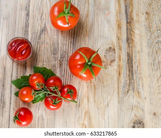 Composition from a tomato and ketchup on a wooden background.