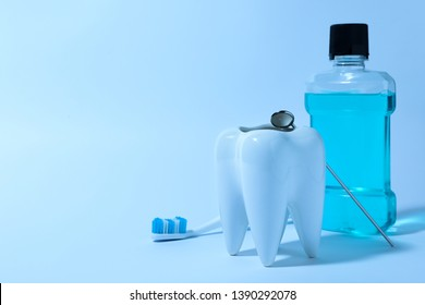 Composition with tooth shaped holder, mouthwash, brush and mirror on color background, space for text. Dentist consultation