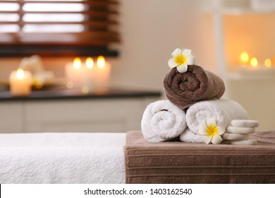 Composition with towels, flowers and stones on massage table in spa salon. Space for text