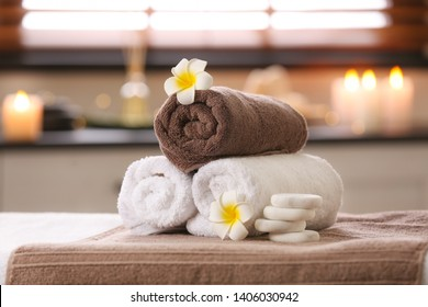 Composition with towels, flowers and stones on massage table in spa salon