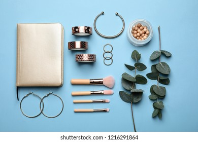 Composition with tropical leaves, makeup brushes and accessories on color background