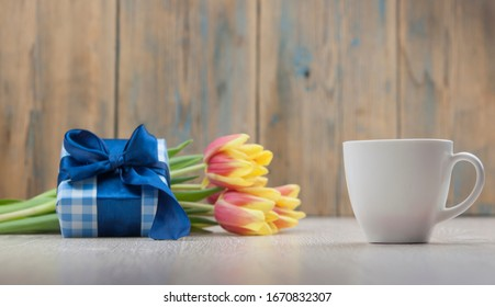 Composition with tulips, coffee cup and gift box on wooden table.
