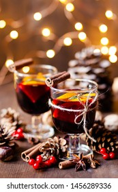 Composition with two glasses of hot mulled red wine with spices. Holiday atmosphere, christmas ligths on dark background. Rustic style, cones, nuts, anise, cinnamon, orang, berries as festive decor