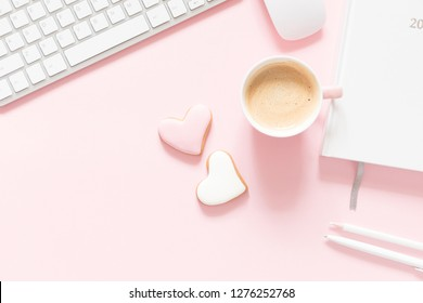 Composition Valentine's Day. Female desktop сomputer keyboard, сup of coffee and ginger cookie in shape heart on pastel pink background. Valentine day concept, design.