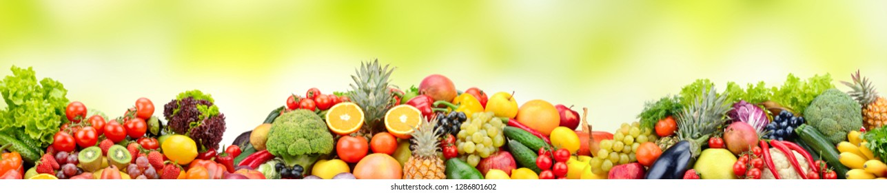 Composition variety fresh fruits and vegetables on green background. Glass skinali.