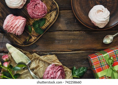 Composition of various blueberry, cherries meringues and flowers on dark wooden background, top view, present box. Copy space for birthday greeting.