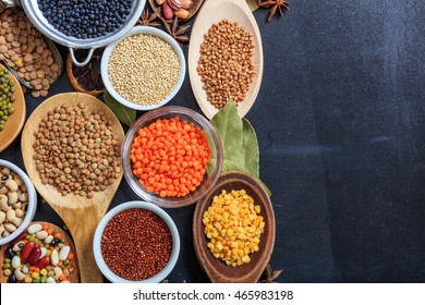 Composition of various kinds of legumes on black background, top view, copy space