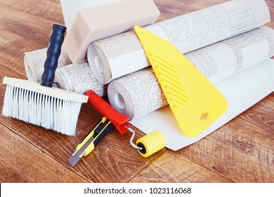 Composition with various tools for home repair and rolls of wallpaper on wooden background