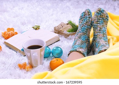 Composition with warm plaid, book,k and female legs, on color carpet background
