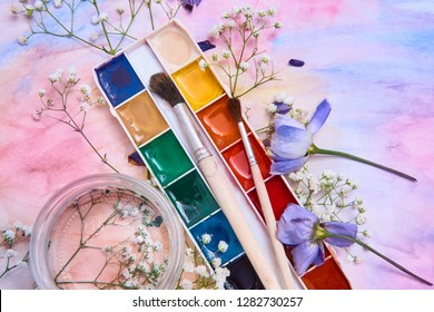 Composition with watercolor paints, brushes, a jar of water, flowers, flower petals, located in the figure with a watercolor background