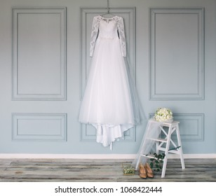 composition - wedding dress on a gray blue wall with decor and accessories