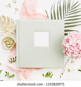 Composition with wedding or family photo album, hydrangea flower bouquet, tropical palm leaf, pastel pink blanket, gold monstera plate on white background. Flat lay, top view mockup concept.