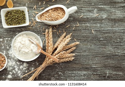 Composition with wheat flour, grains and spikelets on wooden background