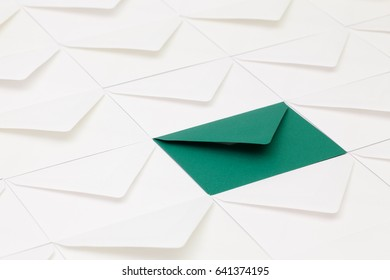 Composition with white envelopes and one dark green  envelope on the table.