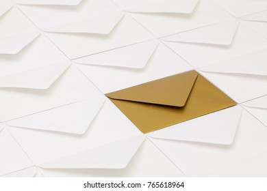 Composition with white envelopes and one gold envelope on the table.