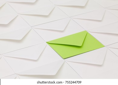 Composition with white envelopes and one green envelope on the table.