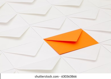 Composition with white envelopes and one orange envelope on the table.