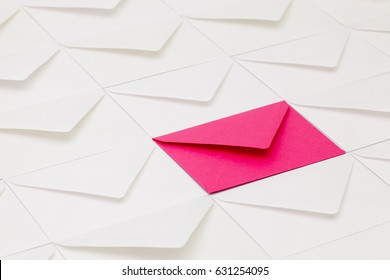 Composition with white envelopes and one pink envelope on the table.