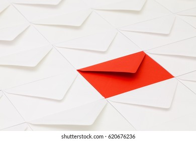Composition with white envelopes and one red envelope on the table.