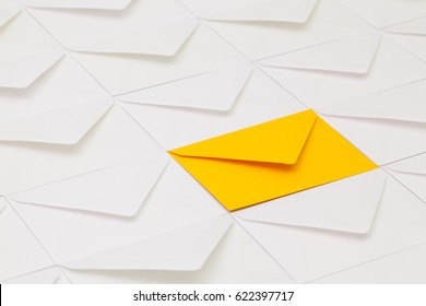 Composition with white envelopes and one yellow envelope on the table.