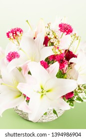 Composition of white lilies bouquet on green graduted background