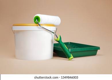 Composition of white paint bucker, paint roller and a green tray for paint