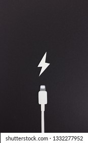Composition of white wire for charging and small icon on black background