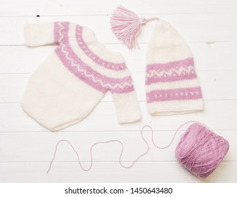 Composition of white-pink knitted suit and hat with decorations